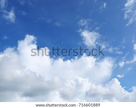 White fluffy puffy clouds spreading in the blue sky on a bright sunny day.