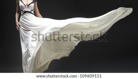 White fluttering dress on black background - stock photo