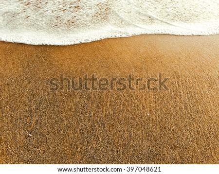White foam wave on yellow sandy beach, high tide, warm sea and sand beach, summer vacation by the sea, seaside travel photo, foam and sand, warm sand on the beach, calm sea, Bali, Indonesia - stock photo
