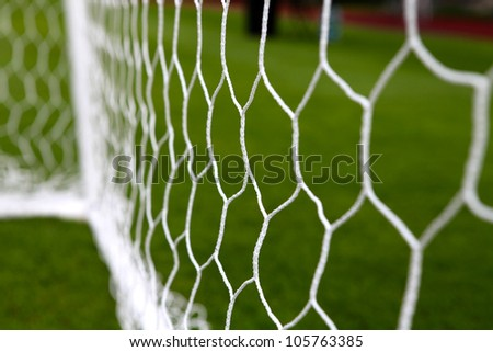 white football net, green grass - stock photo