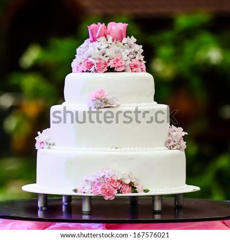 White four tiered wedding cake on table - stock photo