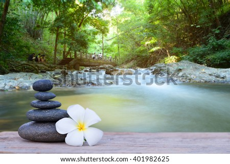 white frangipani flower and stone zen spa on wood with blurred waterfall background - stock photo