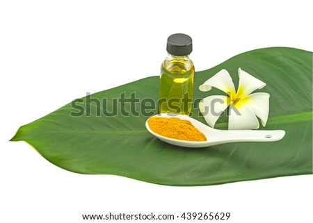 White frangipani flower(Plumeria spp.,Apocynaceae,Pagoda tree, Temple tree flower),turmeric powder in white spoon and massage oil  in green leaf isolate on white background.Saved with clipping path - stock photo