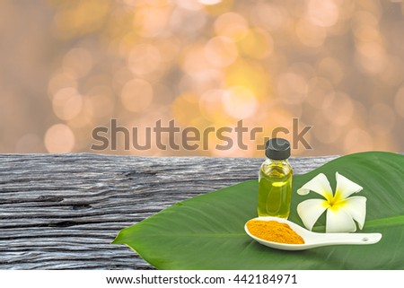 White frangipani flower(Plumeria spp.,Apocynaceae,Pagoda tree, Temple tree),turmeric powder in white spoon and massage oil in green leaf on wooden and orange bokeh background. - stock photo