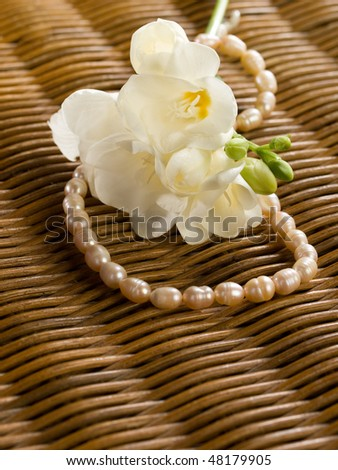white freesia with beads on a wickerworked background - stock photo