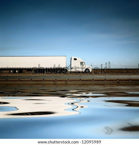 White freight truck driving on freeway under blue sky. - stock photo