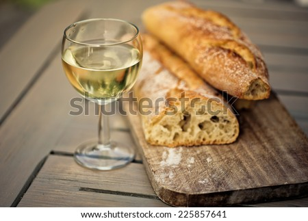 White French Bread on Wooden board with  glass of White Wine - stock photo