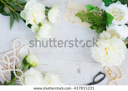 White fresh peony flowers with pearls jewellery on white wooden table frame with copy space