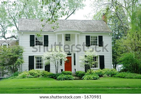 White fromal house with siding, black shutters and bright green, manicured lawn / garden - stock photo