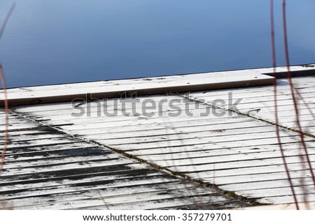 white frost on dock in cold blue water at shoreline closeup - stock photo