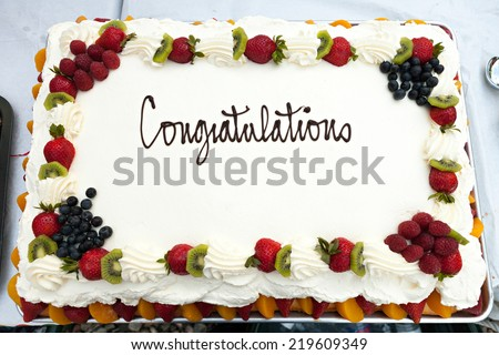 White frosted cake with a fruit border and the message that reads Congratulations. - stock photo