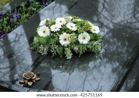 White funeral flowers on a grey marble tomb - stock photo