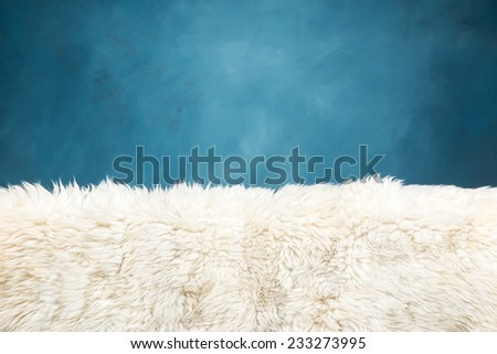 white fur carpet and blue painted wall , use for background - stock photo