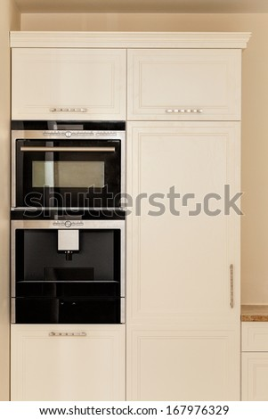 White furniture with black oven in modern kitchen