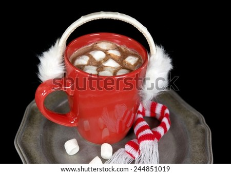 white furry ear muffs on red mug with hot chocolate drink - stock photo