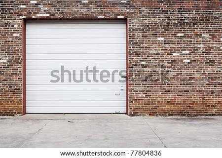 white garage door on brick wall - stock photo
