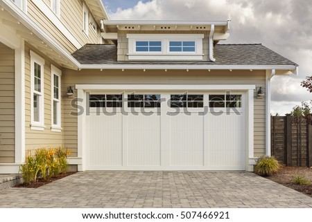 White garage door with a driveway made with brick