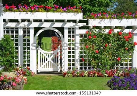 White garden gate and fence in colorful botanical garden - stock photo