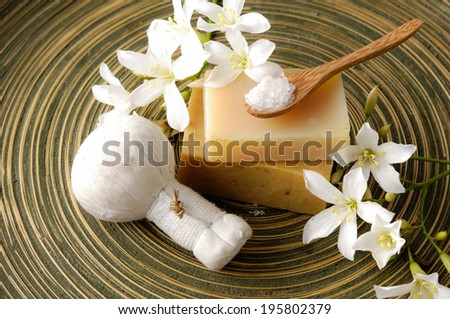 White gardenia flower and massage ball with soap ,spoon on wooden plate  - stock photo