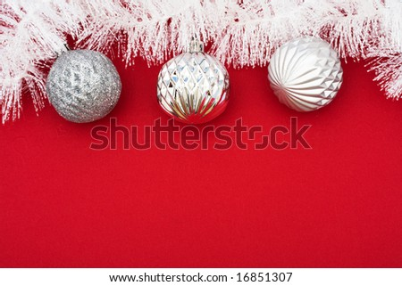 White garland on red background with silver glass balls, Christmas background