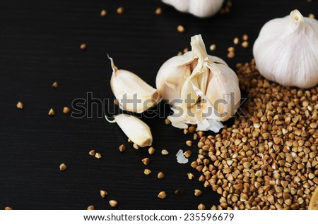 white garlic on buckwheat on a dark table - stock photo