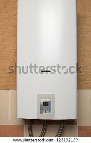 White gas water heater to the wall - stock photo