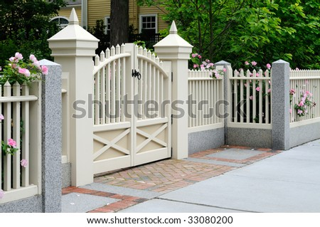 White gate and fence with pink roses on house entrance. Elegance, craftsmanship, home improvement. - stock photo