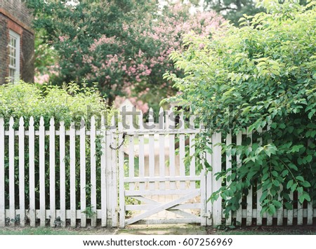 White Gate Surrounded by Flowers and Bushes