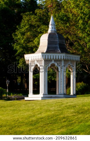 White gazebo in a lush green setting of lawn and trees. Location: Bar Harbor, Maine, USA - stock photo