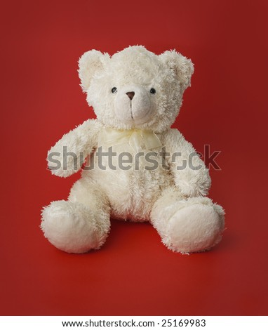 White generic teddy bear sitting on red - stock photo