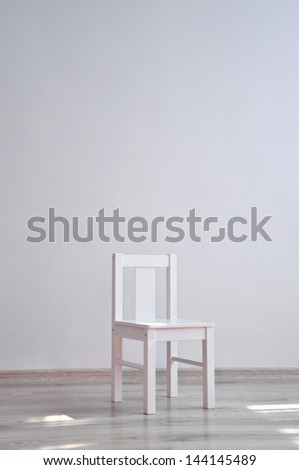 White geometric minimalistic style chair standing in an empty room in front of a wall on light parquet floor. Natural light from the window - stock photo