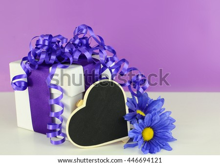 White gift box decorated with purple ribbon. Curly ribbons make a bow on top. A purple silk daisy is beside the box with a heart shaped blackboard. All on a white table with purple background.  - stock photo
