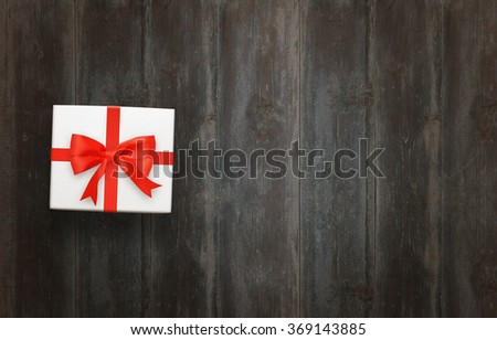 White gift box with red bow on wooden table with free space for text. - stock photo