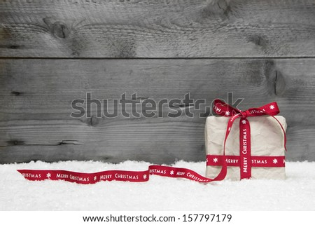 White gift box with red long ribbon and bow on grey wooden background - stock photo