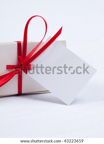 White gift box with red ribbon and blank tag - stock photo