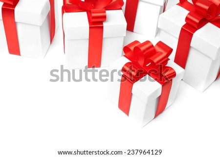 White gift box with red ribbon bow and christmas balls around, isolated on white background