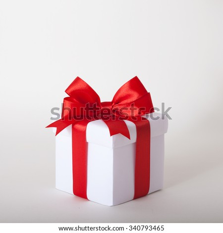 White gift box with red ribbon bow, isolated on gray background