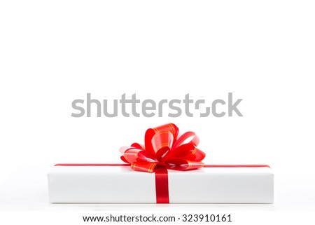 White gift box with red ribbon bow, isolated on white.
