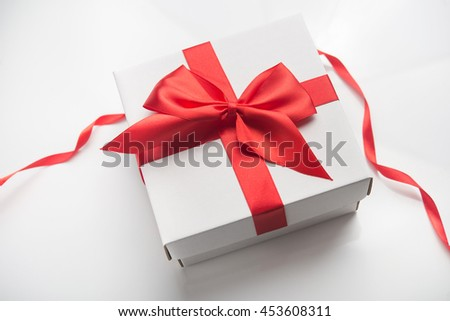 white gift box with red ribbon bow on background