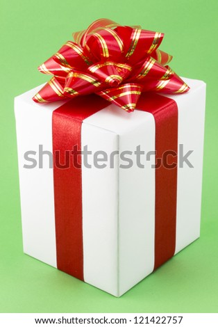 White Gift Box with Red Ribbon Bow on green background