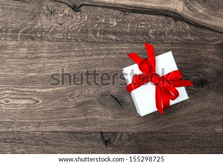 white gift box with red ribbon bow over wooden background - stock photo