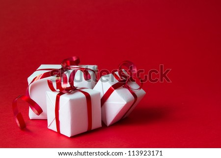 White gift box with red ribbon isolated on red color background - stock photo