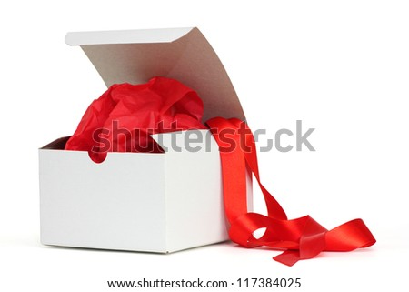 White gift box with red tissue and a red ribbon - stock photo