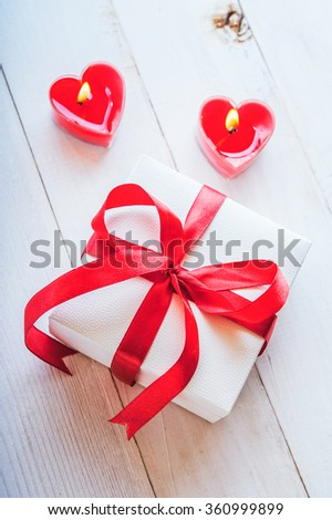 White gift box with ribbon and red candles in the shape of heart