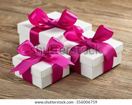 White gift box with violet ribbon on board. - stock photo