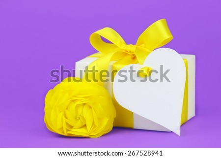 White gift box with yellow ribbon and a bow with a flower and a heart shaped greeting card on purple background with copy space for Mother's Day, Valentine's Day or any other occasion - stock photo