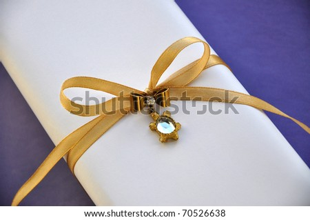 White gift box wrapped with satin golden ribbon and decorated with luxurious pin. Gift box is isolated on blue background.