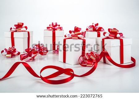 White gift boxes with red ribbons and bows on gray