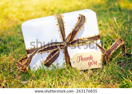 white gift on green meadow - thank you - stock photo