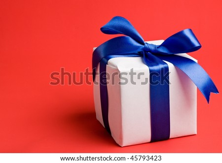 white gift with a blue ribbon on a red background